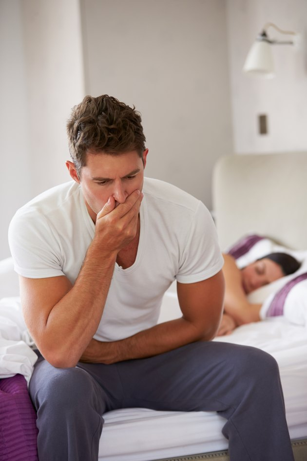 Man Sitting On Bed And Feeling Unwell