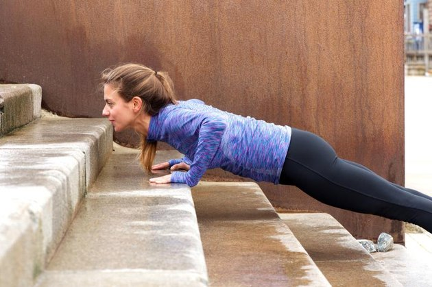 Portrait of serious female athlete in push up on staircase