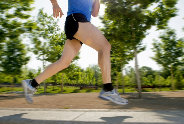 legs of young man running in city park fitness concept