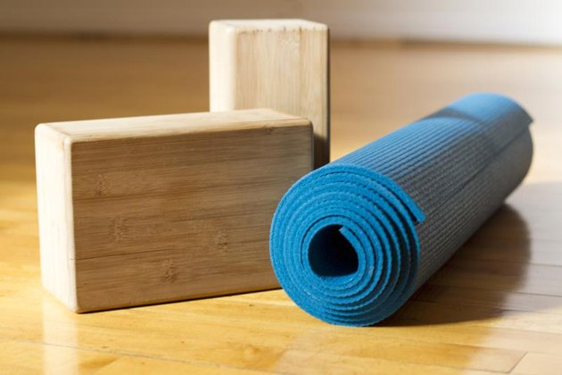A blue yoga mat with two wooden yoga blocks sit on a wooden yoga studio floor before class.
