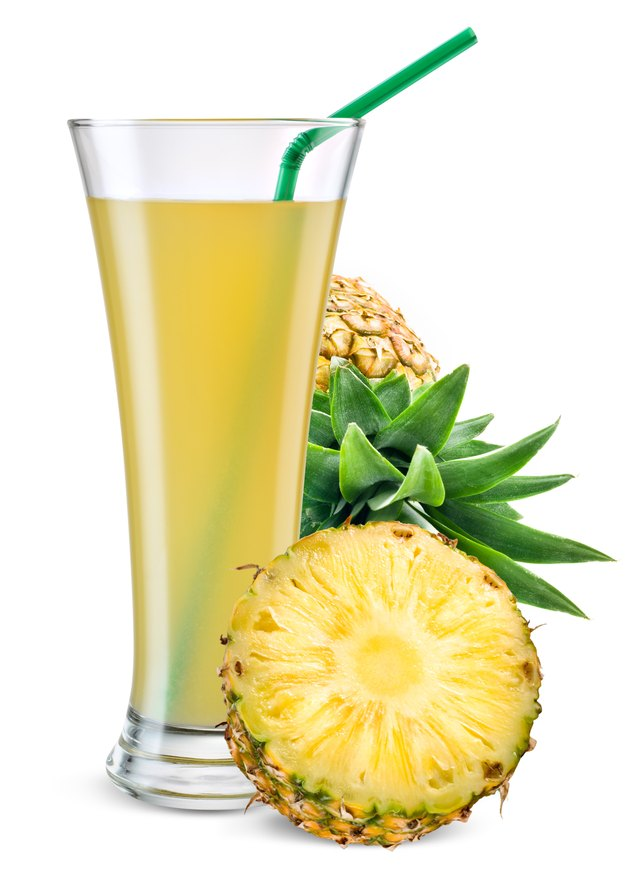 Glass of pineapple juice with fruit isolated on white.