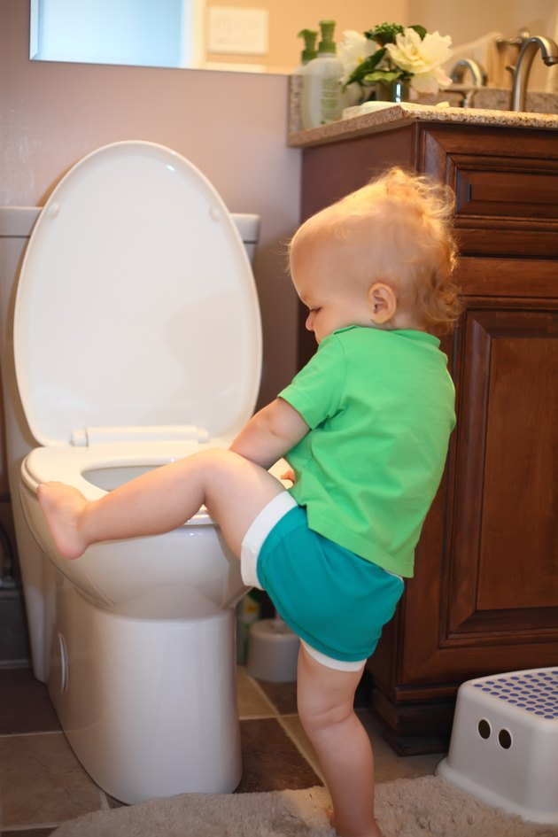 Baby trying to sit on a toilet