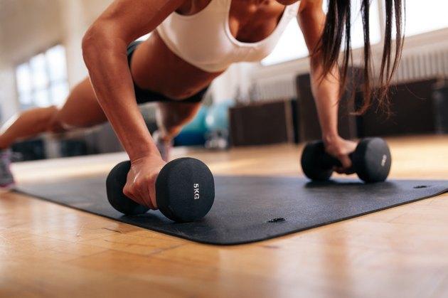 Woman doing pushups on dumbbells