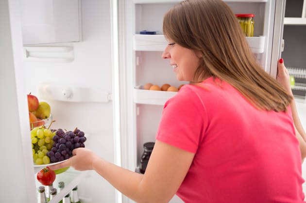 Housewife take plate full of grapes from fridge