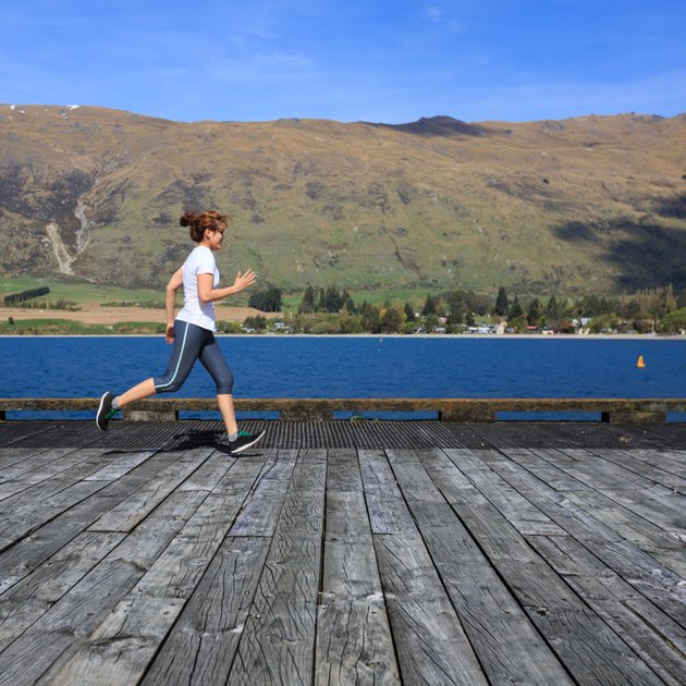 Young adult woman running on pier