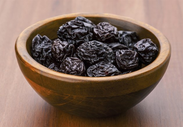 prunes group in wooden bowl