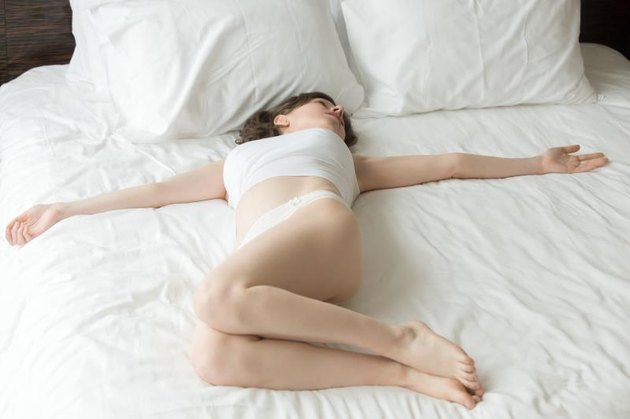 Young pregnant woman working out at home. Caucasian model doing Spinal Twist, Jathara Parivartanasana, resting after morning practice on the bed
