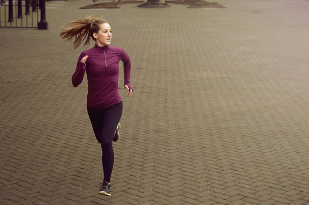 Young woman running along sidewalk