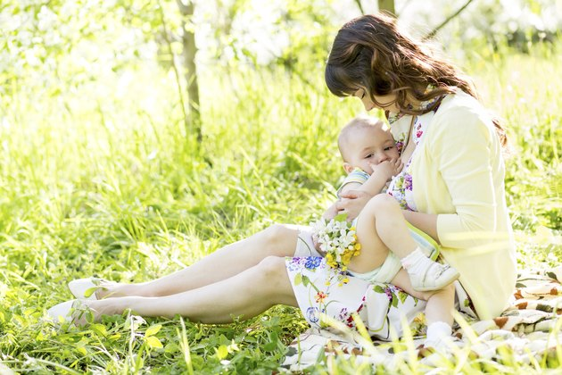 young mother breast feeding her baby outdoors summertime