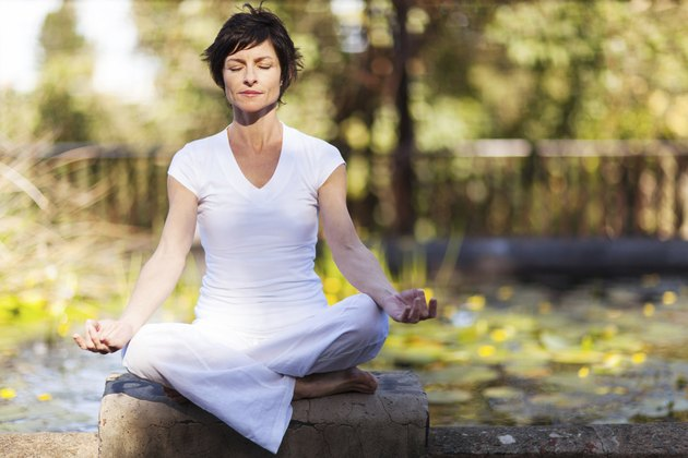 middle aged woman doing yoga meditation