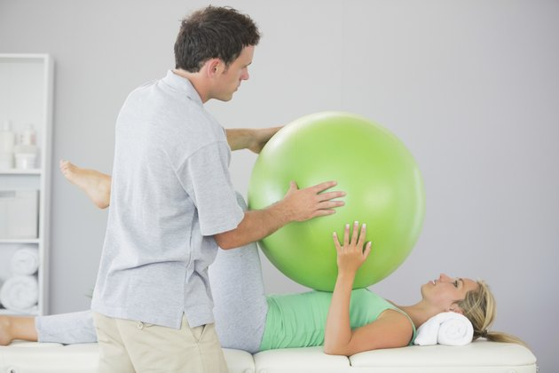 Patient training with exercise ball and physiotherapist