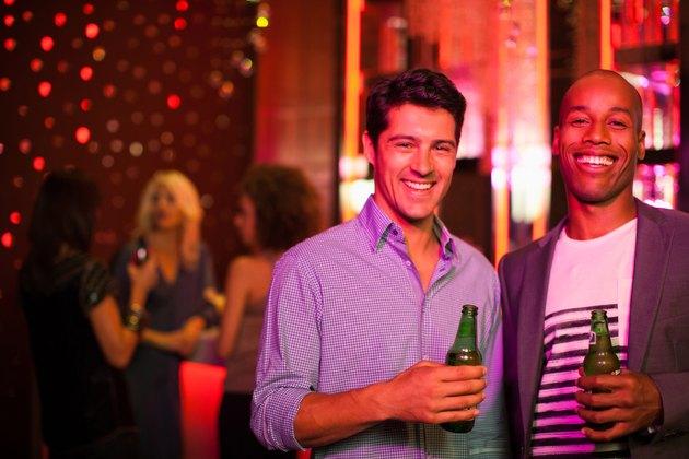 Men holding beer bottles in nightclub