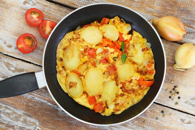 Omelette with potatoes, onions, pepper and sweetcorn in frying pan