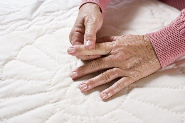 Sore aging hands of senior woman