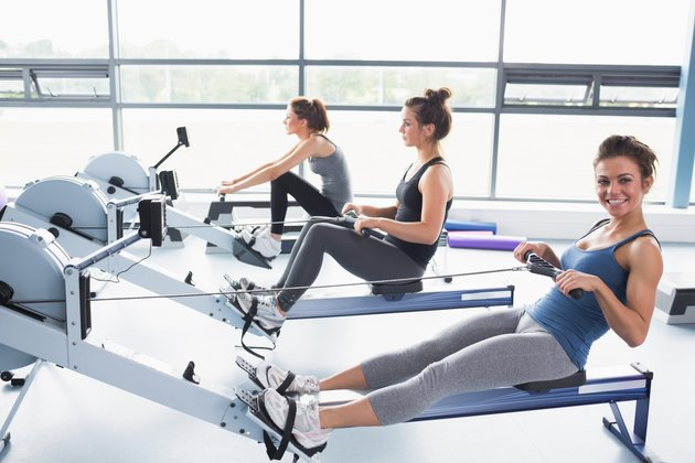 Happy woman using rowing machine with friends