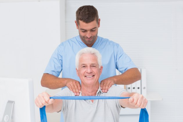 Physiotherapist assisting senior patient in exercising with resistance band