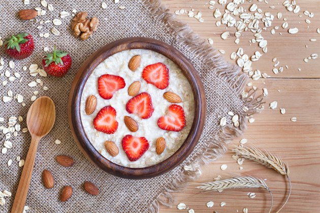Healthy prepared oatmeal porridge breakfast with strawberries and nuts in