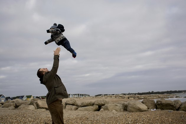Father throwing son in the air at the beach