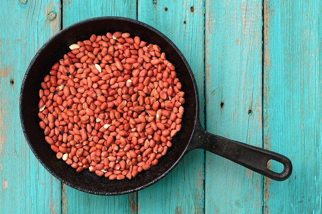 Whole fried pink peanuts in black cast iron pan