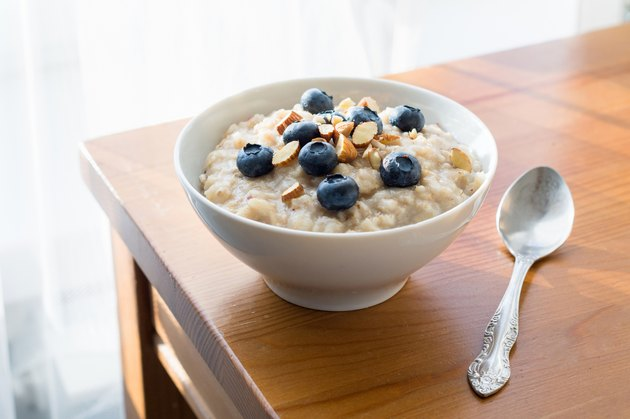 Oatmeal porridge with blueberries and almonds on table