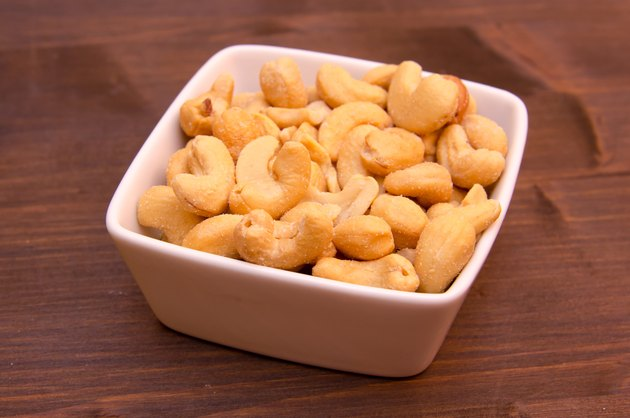 Cashew nuts on bowl on wood