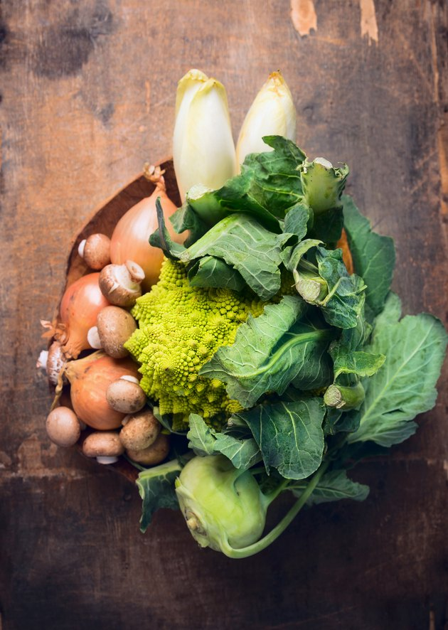 Romanesco with fresh vegetables in dish on rustic wooden background