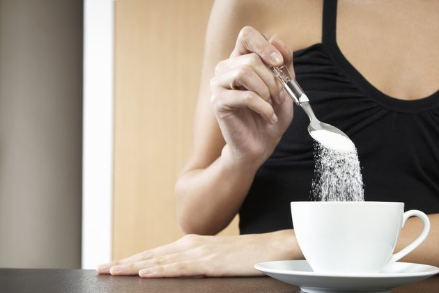 Cropped Woman Pouring Sugar In Tea Cup
