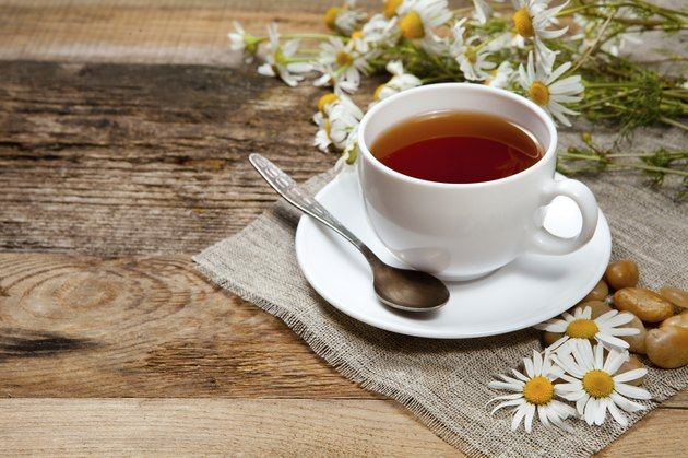 herbal tea with chamomile on old wooden table