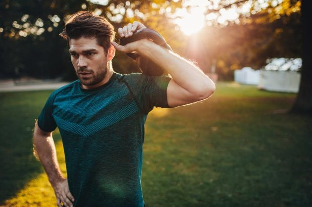 Portrait of strong young man exercising with kettlebell.  Fit and muscular man training at park in morning.