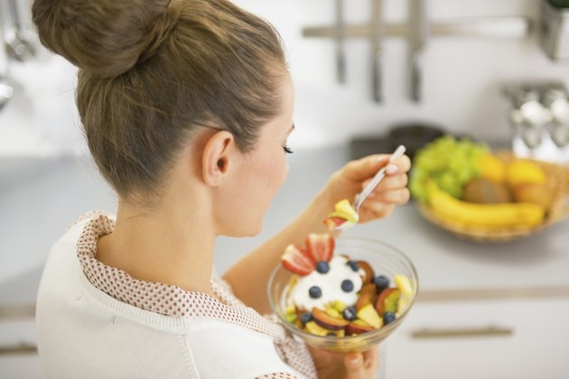 young housewife eating fresh fruit salad. rear view