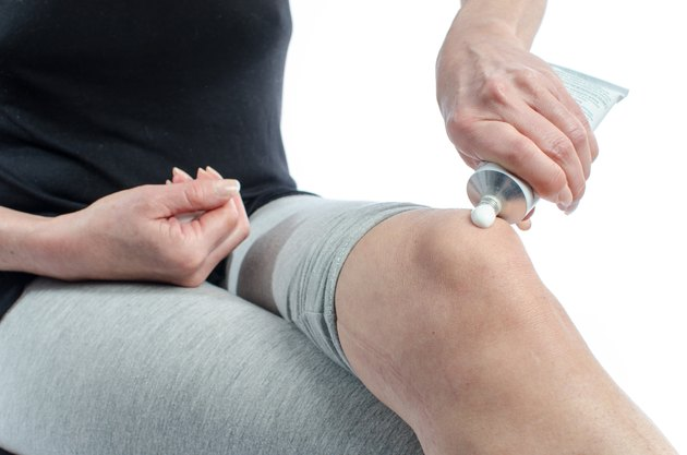 Woman putting cream on her knee