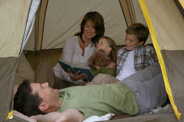 Girl (5-7 years) and boy (9-11 years) in tent with parents, mother reading story