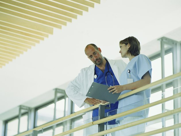 Mature male doctor and young female nurse holding folder by railing