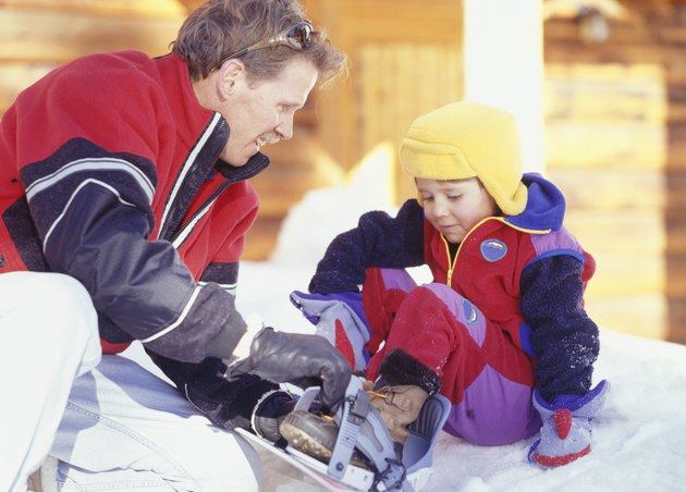 Man helping son (4-5) with snowboard