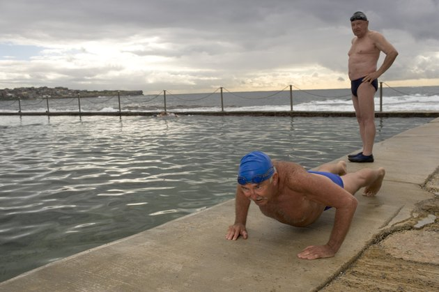 Two senior men at side of infinity pool, one doing press-ups