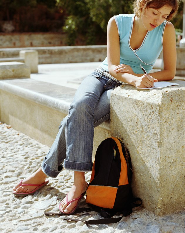 Young woman sitting in sunshine on step writing letter