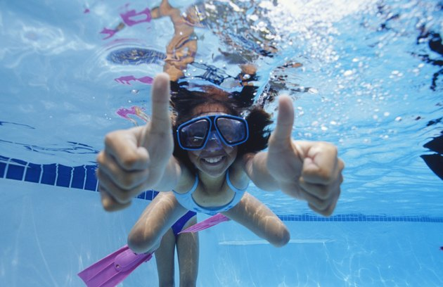 Girl (8-9) swimming underwater, showing thumbs up, underwater view