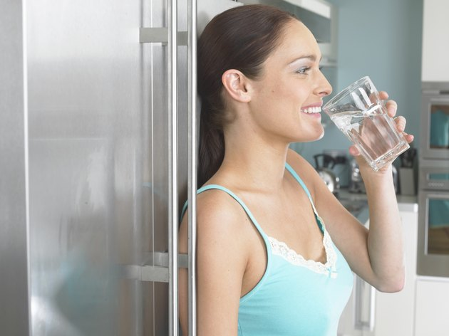 Young woman leaning against fridge, drinking glass of water, side view