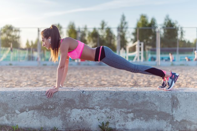 Fitness woman doing push ups Outdoor training workout summer evening