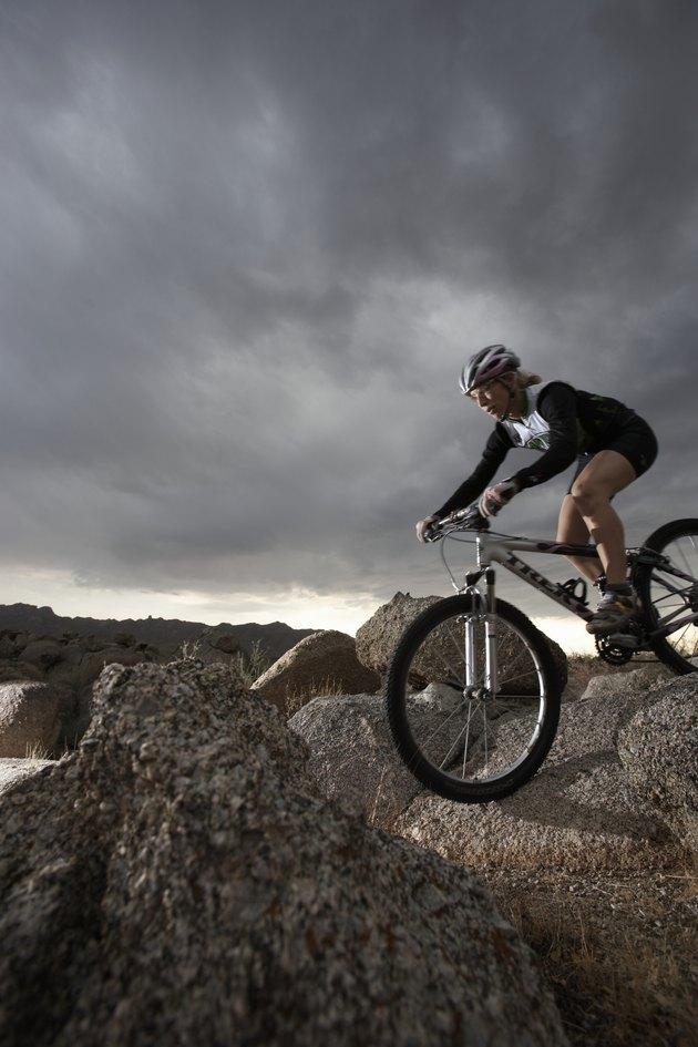 Female rider mountain biking between rocks, side view