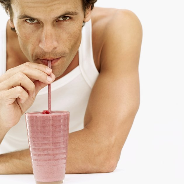 Portrait of a man drinking juice from a glass with a straw