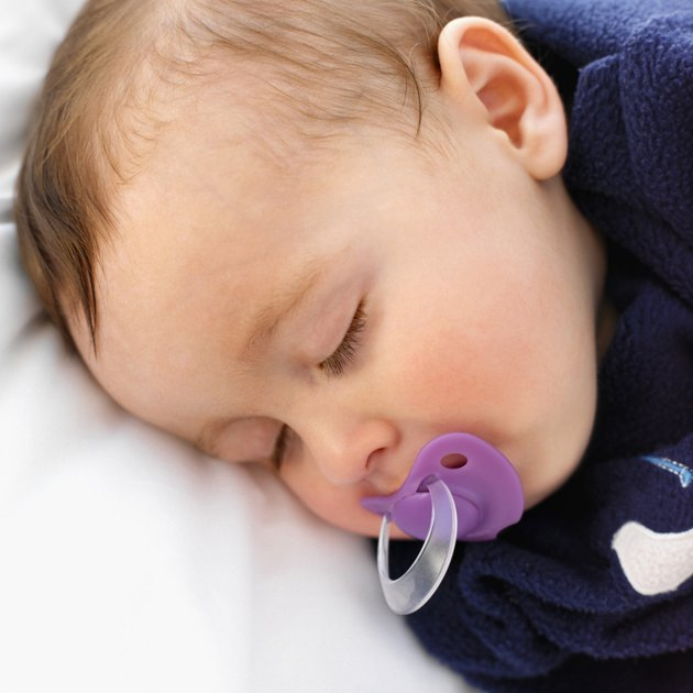 elevated close up view of a baby (6-12 months) sleeping with a dummy in its mouth