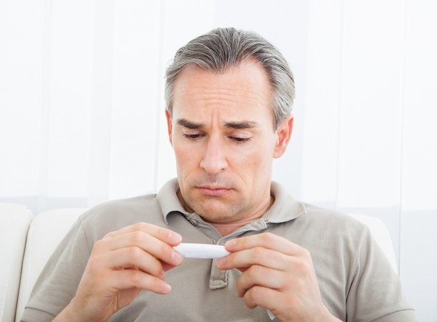 Mature sick man looking at thermometer