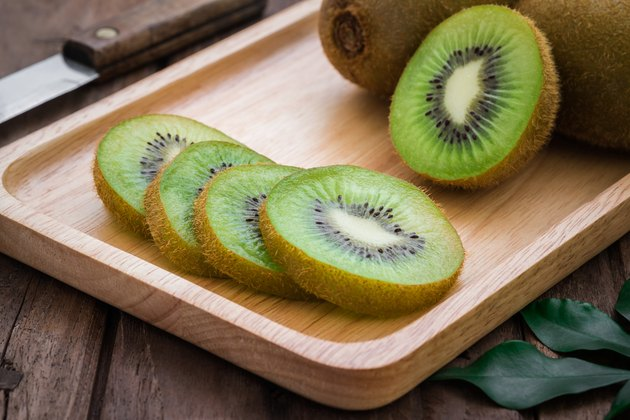 Kiwi fruit slices on wooden plate