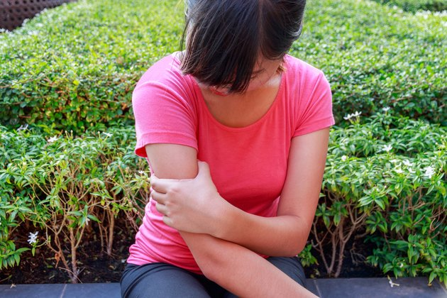 Female arm pain sitting in the park