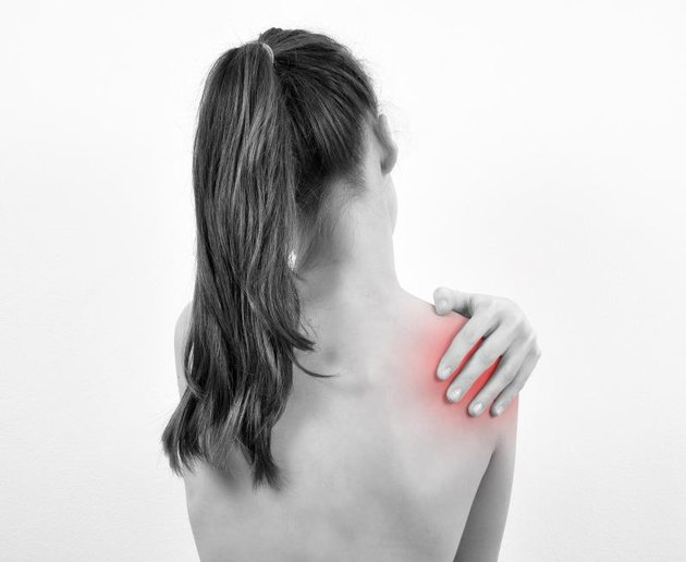 Girl having shoulder pain isolated on the white background. Black and white photo.