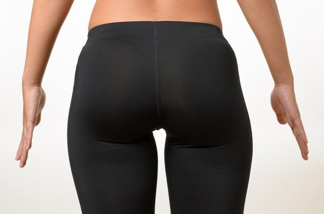Toned buttocks and thighs of a shapely young woman holding her hands away from her sides isolated on white, close up view
