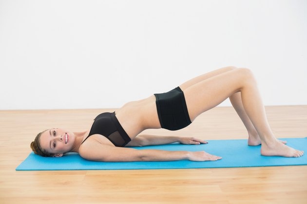 Gleeful young woman in sportswear lying on exercise mat doing exercises