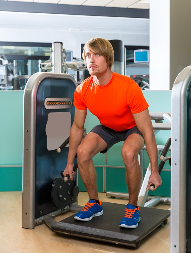 Gym squat machine exercise workout blond man