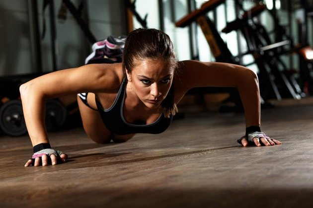 Sporty young woman doing a pushups at gym.